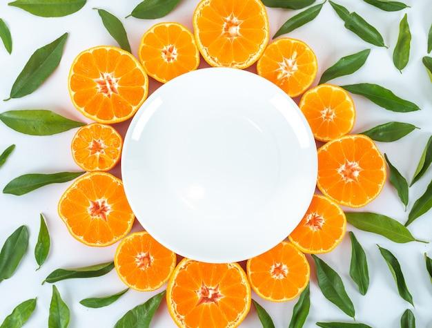 Piatto vuoto circondato con frutti arancioni e foglie vista dall'alto