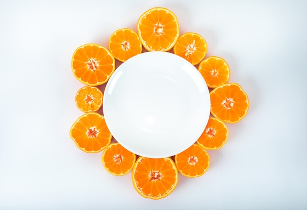 Empty plate surrounded with sliced mandarins with copy space on white surface