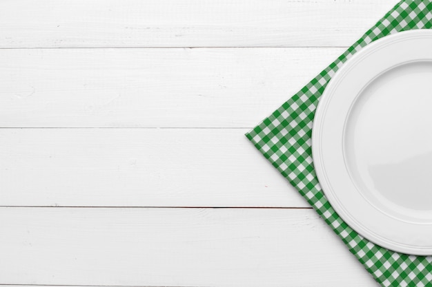 Empty plate and towel over wooden surface table
