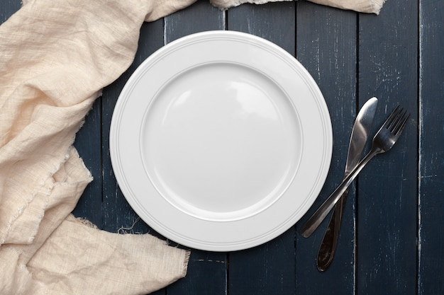 Empty plate and towel over wooden table background