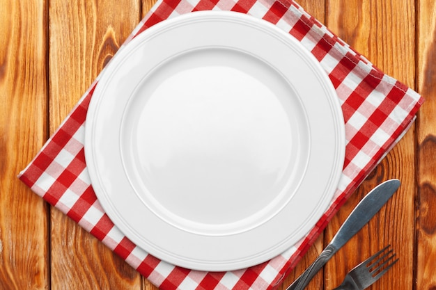 Empty plate and towel over wooden table