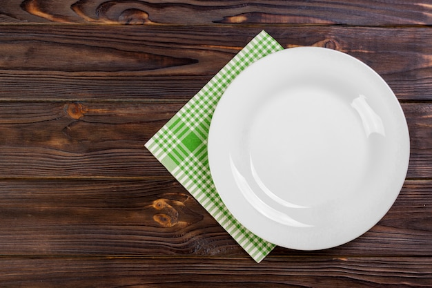 Empty plate and towel over wooden table.