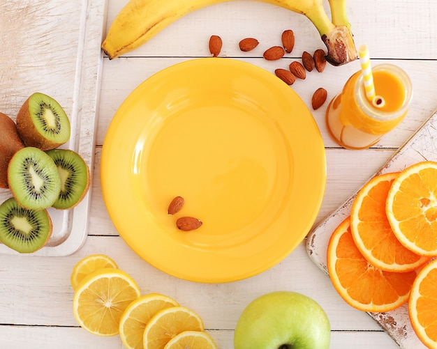 Empty plate and various fruits around