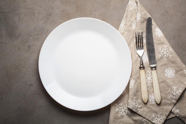 Empty plate with cutlery and beige towel with snowflakes.