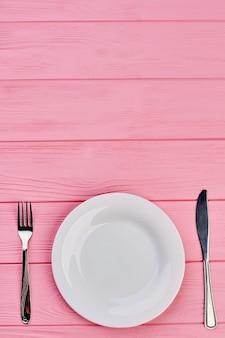 Пустую тарелку вилкой и ножом. розовый деревянный фон с тарелкой, серебряной вилкой и ножом с копией пространства сверху, вид сверху.