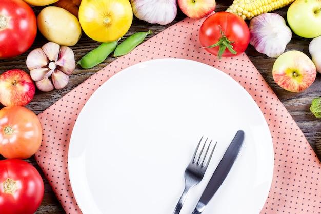 Пустая тарелка с вилкой и ножом в окружении свежих овощей, концепция здорового питания