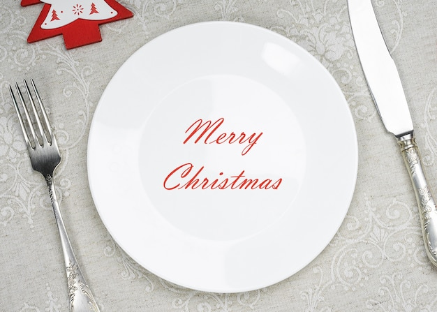 Empty plate with inscription merry christmas with xmas and new year decorations for holiday menu.