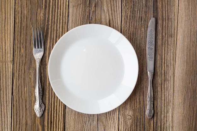 Пустая тарелка с ножом и вилкой на пустой деревянный стол