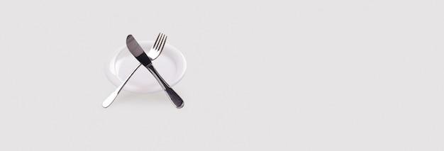 Пустая тарелка с ножом и вилкой