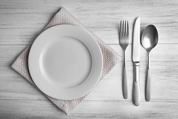 Пустая тарелка с серебряными столовыми приборами на деревянном фоне