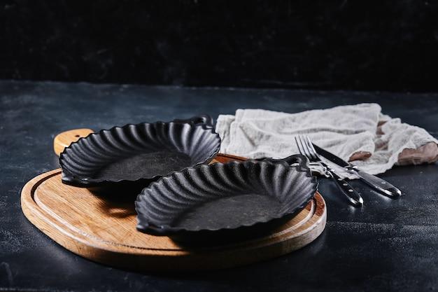 ボケ味の背景の上の木製のテーブルに銀器と空のプレート。