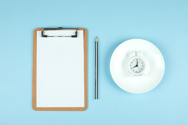 Empty plate with white alarm clock and white note