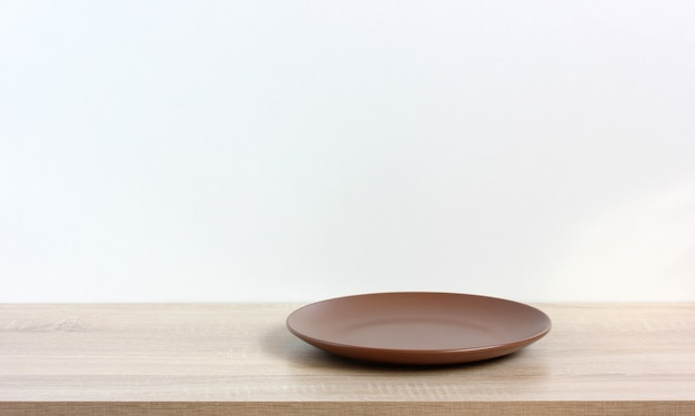 An empty plate on a wooden table or shelf