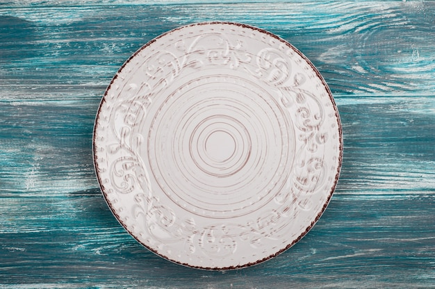 Empty plate over wooden table