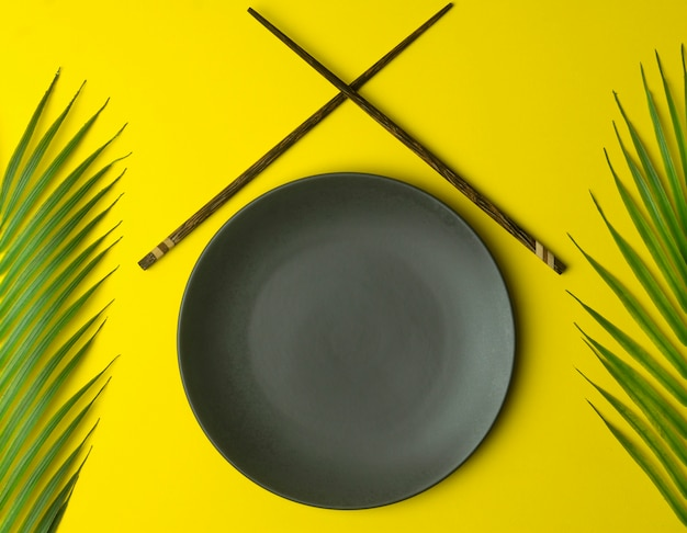 Empty plate on a yellow background. empty plate for asian and chinese food and cuisine with chinese chopsticks