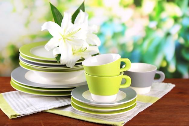 Пустые тарелки и чашки на деревянном столе на зеленой поверхности