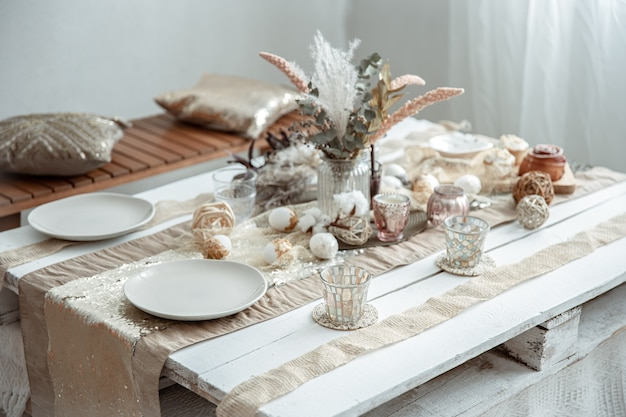 Empty plates and glasses on a decorated dining table for the easter holiday. beautiful hygge-style table setting.