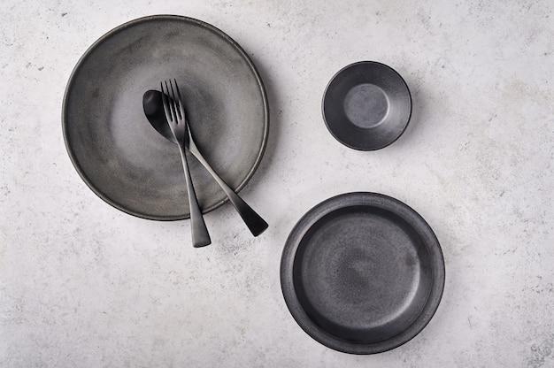 Пустые тарелки, ложка и вилка для соуса, темная кухонная утварь, установленная на светло-серой плоской поверхности стола