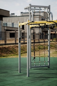 Пустая детская площадка с турниками, перекладинами и брусьями. спорт на природе в городском зеленом парке.