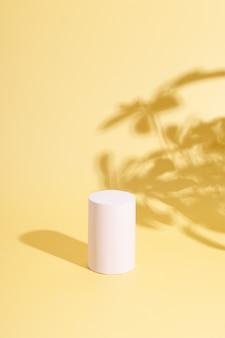 空の表彰台と暑い太陽の下での熱帯の葉の影。あなたの製品のための創造的な夏のモックアップ