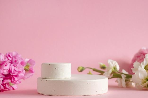化粧品のプレゼンテーションのための空の表彰台。ピンクの背景の側面図にパステルの花