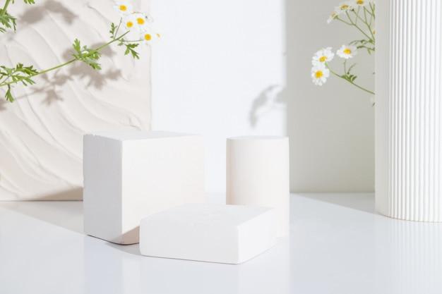 흰색 배경에 카모마일 꽃이 있는 빈 연단이나 받침대. 빈 선반 제품 서 배경