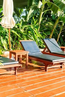 우산과 햇빛이 있는 수영장 주변의 빈 수영장 침대