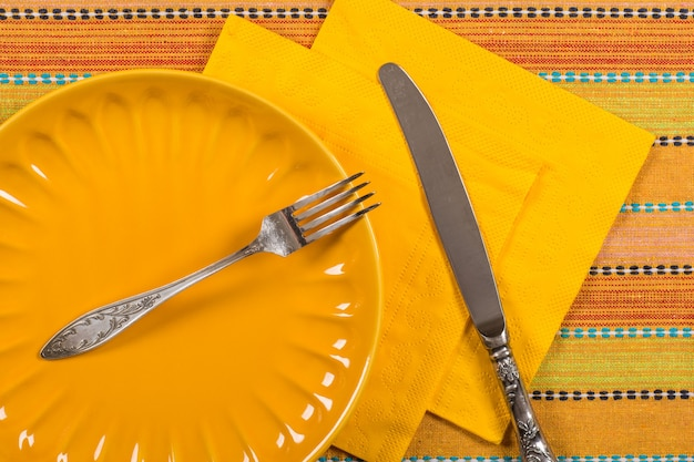 Empty porcelain plate and fork on tablecloth background