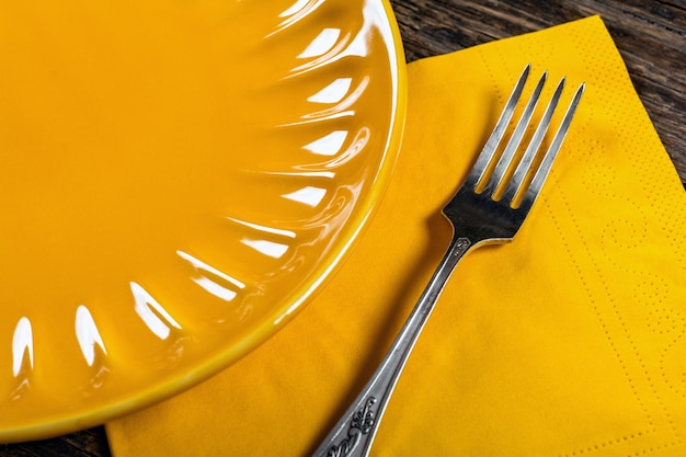 Empty porcelain plate and fork on wooden background