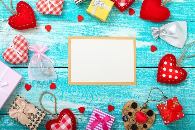 木製のテーブルにギフトボックスとハートの空のポストカード。