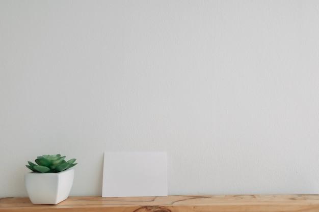 Макет пустой открытки с горшком кактуса на белой стене