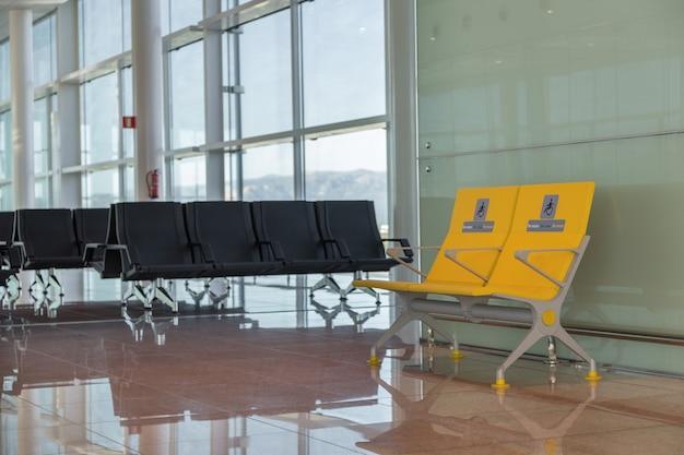 障害者のために予約された国際空港の空の優先席。搭乗前の待機エリアの通常および黄色の障害者用座席。