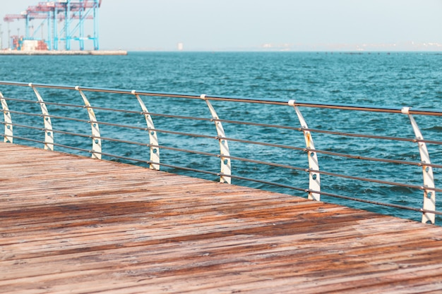 Empty promenade on a sunny day. metal railings and wooden beams of a terrace along the sea