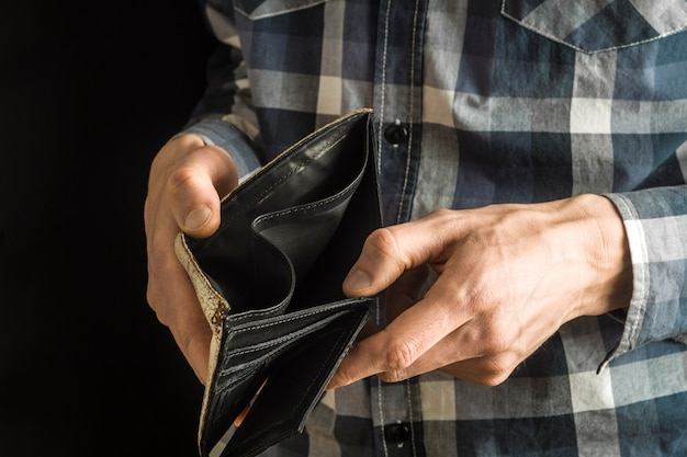 An empty purse in the hands of a man. poverty in retirement concept