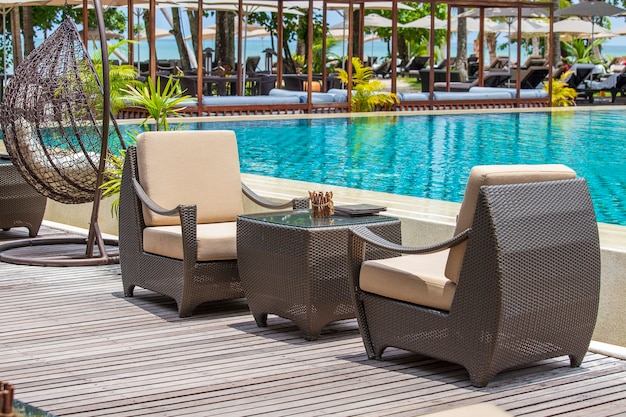 Empty rattan table and chairs on the terrace next to the tropical beach and the sea, thailand