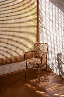 Пустой плетеный стул из ротанга с солнечным светом, пробивающимся сквозь деревянные жалюзи в доме