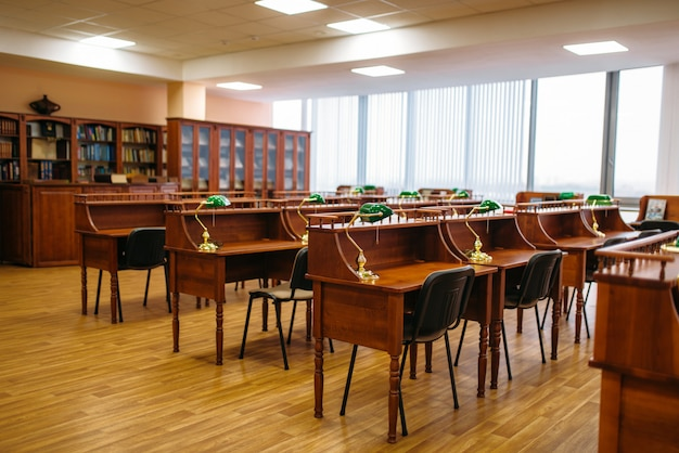 Empty reading room, rows of tables in library, nobody. knowledge depository, shelf with books, education concept