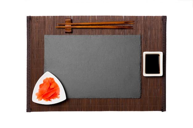 Пустая прямоугольная черная грифельная тарелка с палочками для суши, имбиря и соевого соуса на циновке из темного бамбука. вид сверху с копией пространства для вашего дизайна