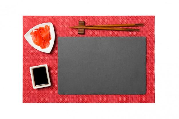 Пустая прямоугольная черная грифельная тарелка с палочками для суши, имбирем и соевым соусом на красных матовых суши. вид сверху с copyspace для вашего дизайна