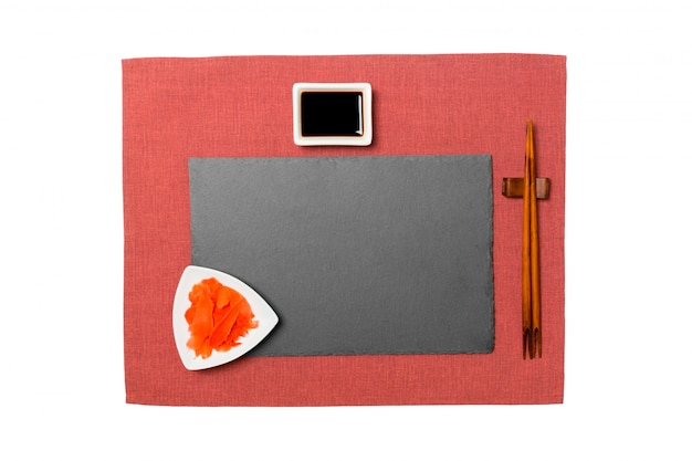 Empty rectangular black slate plate with chopsticks for sushi, ginger and soy sauce on red napkin background