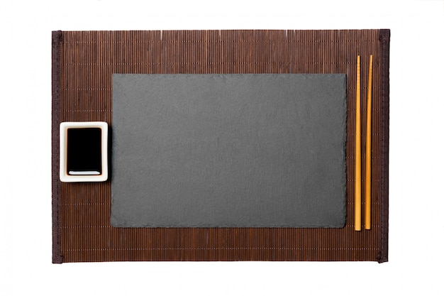 Empty rectangular black slate plate with chopsticks for sushi and soy sauce on dark bamboo mat background.