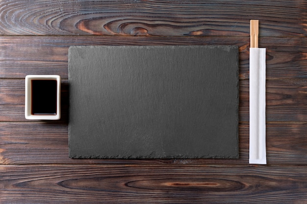 Empty rectangular black slate plate with chopsticks for sushi and soy sauce on wood