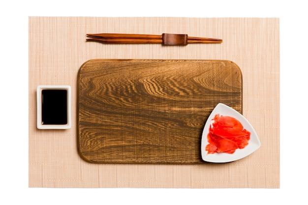 Пустая прямоугольная коричневая деревянная тарелка с палочками для суши, имбирем и соевым соусом на коричневой поверхности коврика для суши