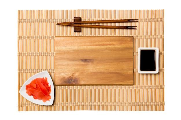 Пустая прямоугольная коричневая деревянная тарелка с палочками для суши, имбиря и соевого соуса на желтой бамбуковой циновке
