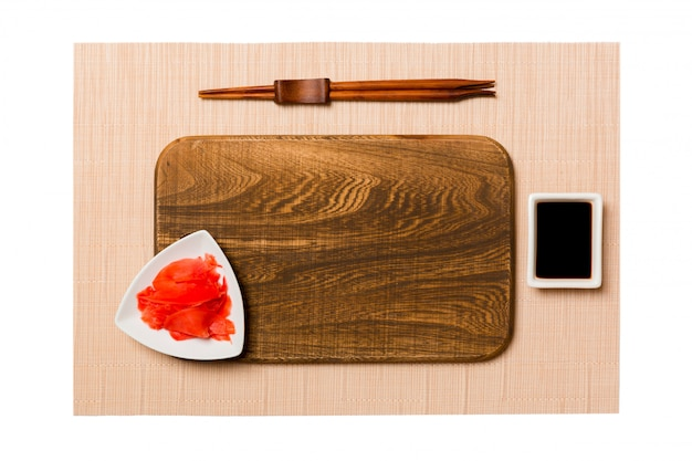 Empty rectangular brown wooden plate with chopsticks for sushi, ginger and soy sauce on brown sushi mat background. top view with copy space for you design
