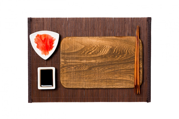 Empty rectangular brown wooden plate with chopsticks for sushi, ginger and soy sauce on dark bamboo mat . top view with copyspace