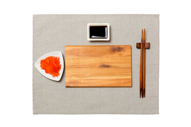 Empty rectangular brown wooden plate with chopsticks for sushi, ginger and soy sauce on grey napkin . top view with  copyspace