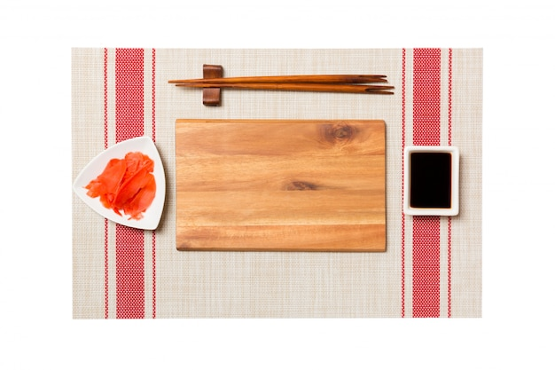 Empty rectangular brown wooden plate with chopsticks for sushi, ginger and soy sauce on sushi mat background. top view with copyspace