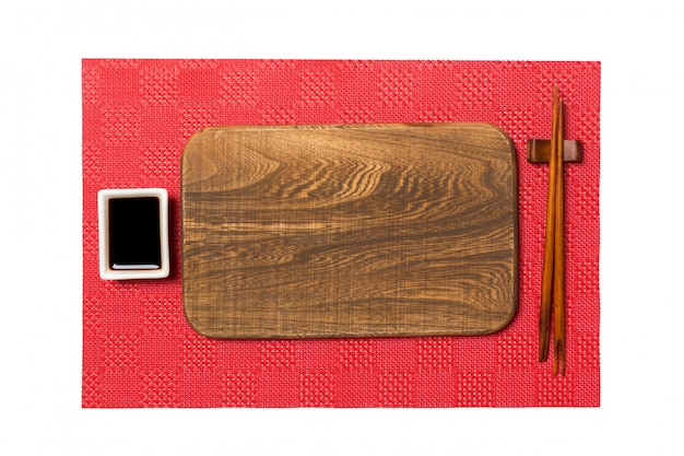 Empty rectangular brown wooden plate with chopsticks for sushi and soy sauce on red mat sushi background