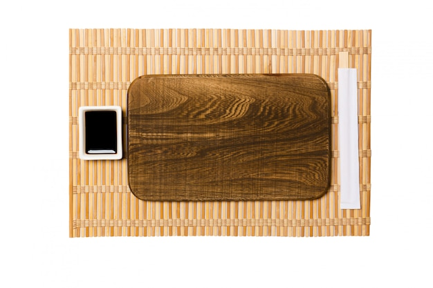 Empty rectangular brown wooden plate with chopsticks for sushi and soy sauce on yellow bamboo mat